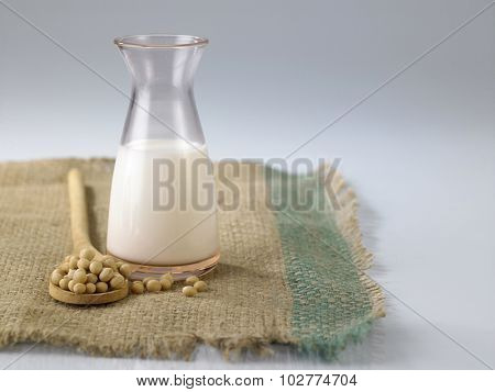 soy bean and jar of the soy milk by the side