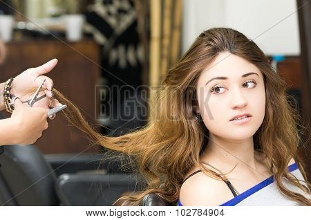 Brunette getting hair done by stylist hands while looking sideways