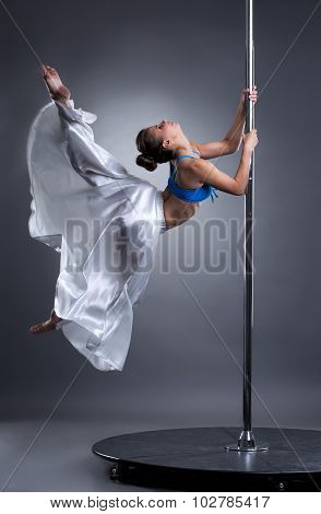 Beautiful girl turning gracefully around pylon