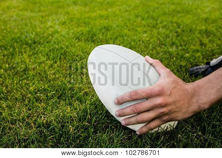 Rugby player picking up ball at the park