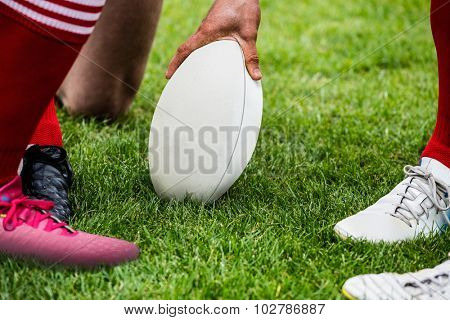 Rugby players in huddle with ball at the park