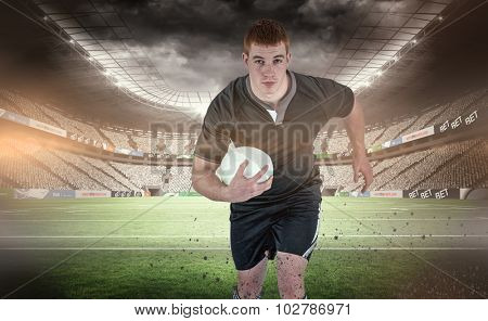 Rugby player running with a rugby ball against rugby stadium