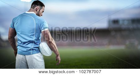 Rugby player standing with ball against pitch
