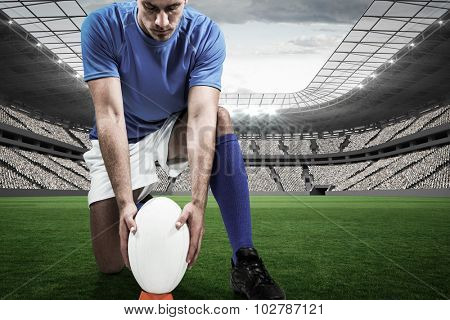 Full length of rugby player placing ball against sports stadium