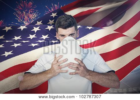 Portrait of serious rugby player holding the ball against fireworks exploding over football stadium