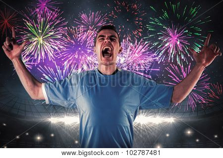 Rugby player gesturing fingers crossed against fireworks exploding over football stadium