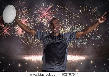 Confident sportsman with arms raised holding rugby ball against fireworks exploding over football stadium