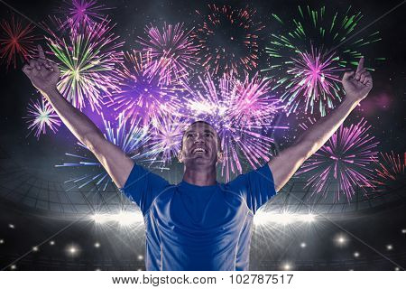 Happy rugby player with arms raised against fireworks exploding over football stadium