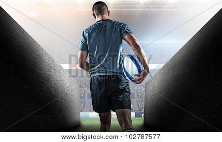 Rear view of rugby player running with ball against rugby stadium