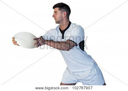 Rugby player leaning over while holding the ball against white background
