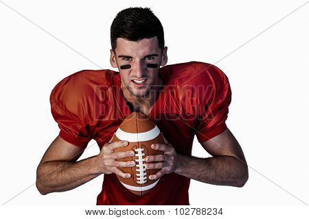 Portrait of serious player holding rugby ball over white background