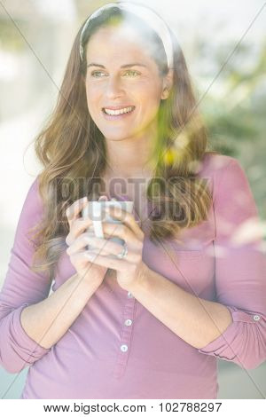 Happy woman with coffee cup standing by window at home