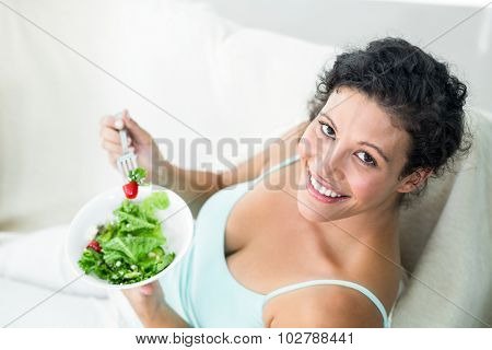 Portrait of happy pregnant woman eating salad on sofa at home