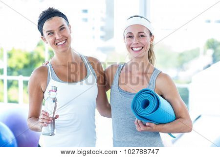 Portrait of women smiling while holding water bottle and yoga mat in fitness studio