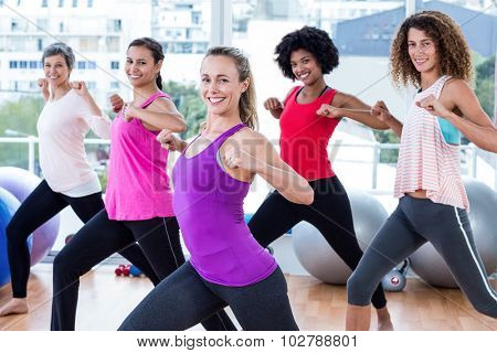 Portrait of women exercising with clasped hands and stretching in fitness studio