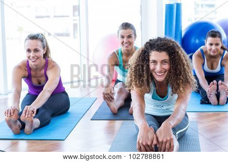 Portrait of woman doing forward bend pose with friends in fitness studio