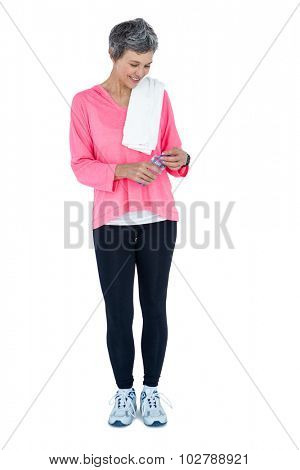 Full length of happy woman with towel on shoulder holding bottle against white background