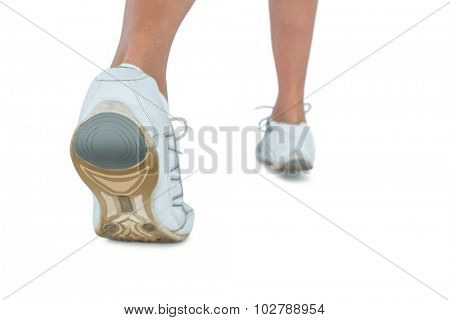 Low section of woman wearing sports shoe jogging over white background