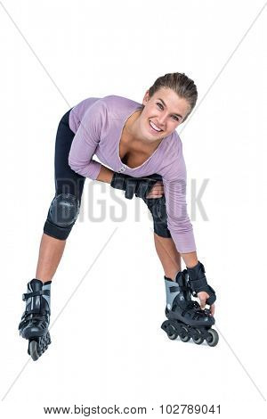 Portrait of happy woman inline skating over white background