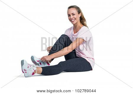 Portrait of sporty woman smiling while tying shoelace over white background