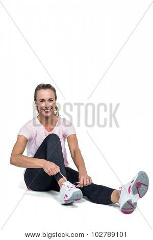 Portrait of woman smiling while tying shoelace over white background