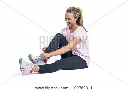 Sporty woman smiling while tying shoelace over white background