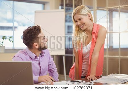 Happy business people talking to eachother by desk desk in creative office