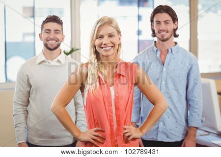 Portrait of smiling businesswoman standing with hands on hip with male colleagues at meeting room in creative office