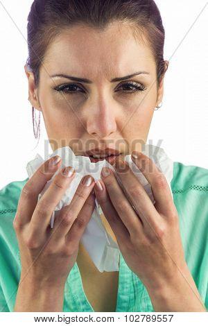 Portrait of sneezing woman holding tissue against white background