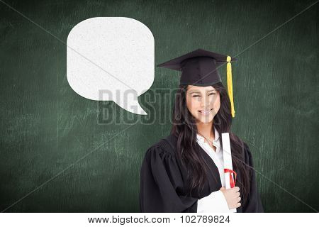 A woman standing to the side slightly with her degree and dressed in her graduation robe against green chalkboard