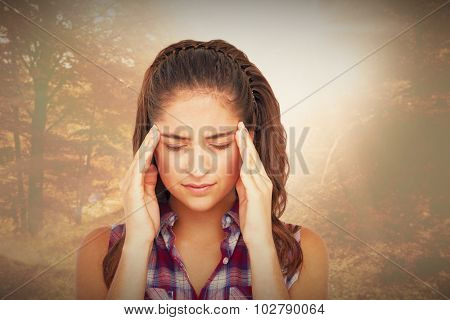 Upset woman suffering from headache against forest trail