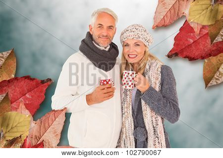Portrait of happy couple drinking hot coffee against low angle view of sky
