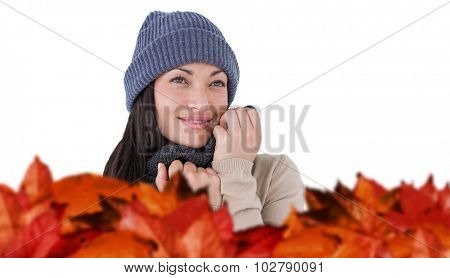 Attractive brunette looking up wearing warm clothes against autumn leaves