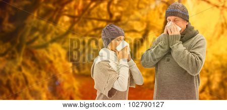 Sick mature couple blowing their noses against peaceful autumn scene in forest