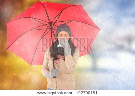 Sick brunette blowing her nose while holding an umbrella against autumn turning to winter