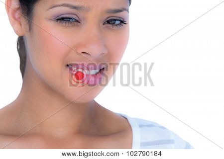 Portrait of beautiful woman biting lips against highlighted pain