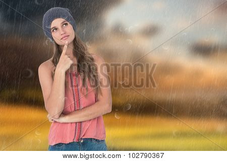 Thoughtful woman wearing hat with finger on chin against country scene