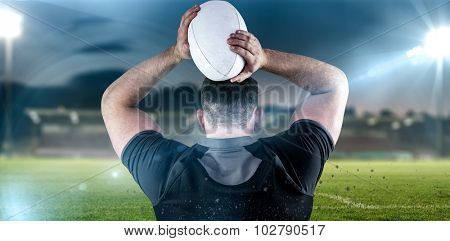 Tough rugby player throwing ball against pitch