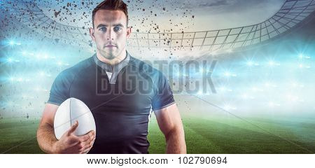 Tough rugby player holding ball against rugby stadium