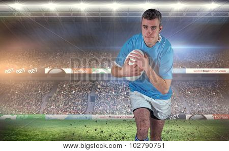 Rugby player running with the rugby ball against rugby stadium