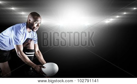 Rugby player looking away while keeping ball on kicking tee against spotlight