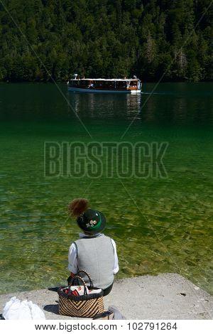 Boy Sitting On Lake Bank And Passer Boat