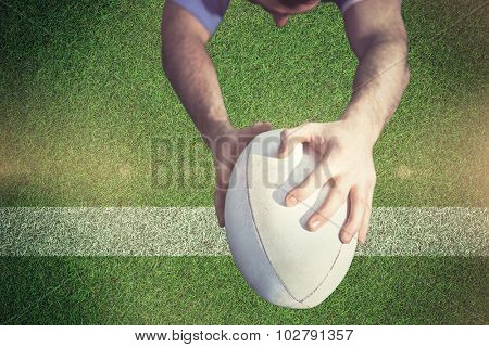 Rugby player ready to tackle the opponent against pitch with line