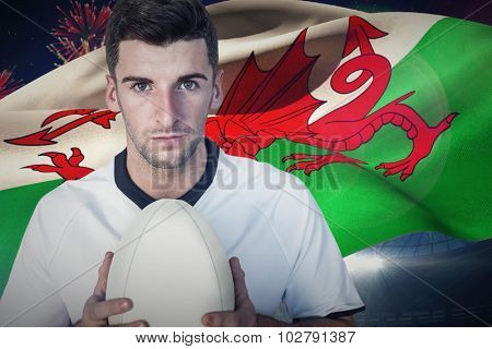 Portrait of a player holding rugby ball against fireworks exploding over football stadium
