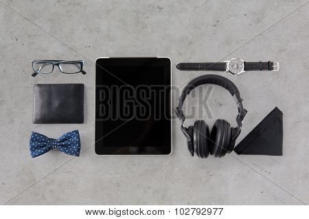 hipster personal stuff and objects concept - tablet pc computer, headphones, wallet, eyeglasses and wristwatch over gray concrete background
