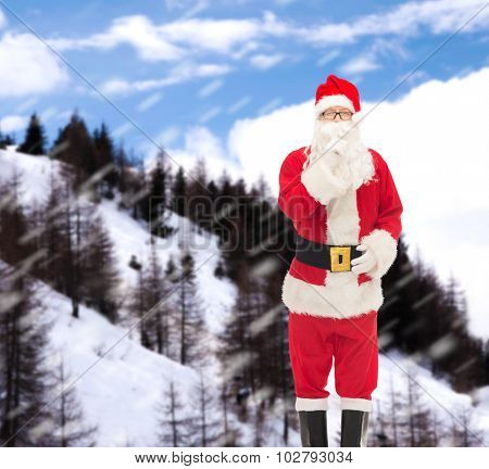 christmas, holidays and people concept - man in costume of santa claus making hush gesture over snowy mountains background