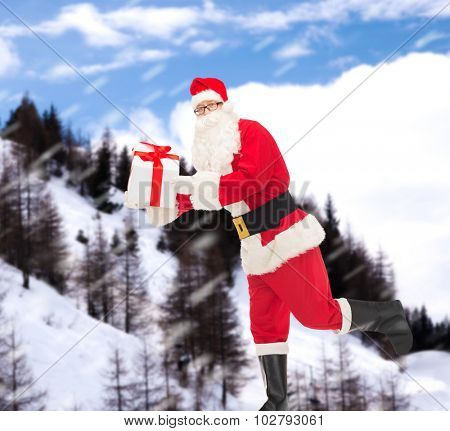 christmas, holidays and people concept - man in costume of santa claus running with gift box over snowy mountains background