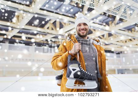 people, sport and leisure concept - happy young man with ice-skates on skating rink