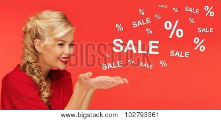 people, holidays, sale, shopping and advertisement concept - lovely woman in red clothes holding something on palms of her hands over red background with sale and percentage signs