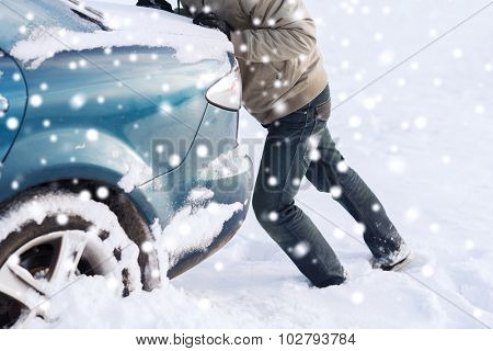 transportation, winter, people and vehicle concept - closeup of man pushing car stuck in snow